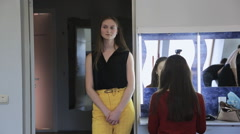 Beautiful girl in yellow trousers stands in dressing room Stock Footage