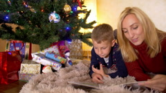 Mom read book with son under a new year tree Stock Footage