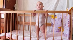 Beautiful happy baby girl standing in bed and looking with interest Stock Footage