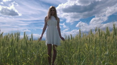 Slow motion - Portrait of a young woman in a dress standing in the wheat field Stock Footage