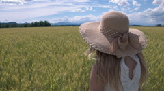 Slow motion - Young female with a sunhat squatting in green wheat field Stock Footage