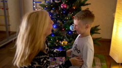 Mother tickling her cute son under christmas tree Stock Footage