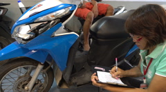 Samui, Thailand - Asian service worker examine motobike damage Stock Footage