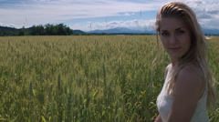 Jib shot - Young woman squats in wheat field and looks into the camera Stock Footage
