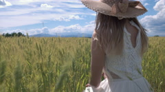 Jib shot - Young woman squatting in wheat field and looking into distance Stock Footage