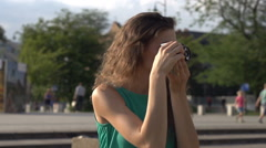Girl doing photos on old camera in town, steadycam shot, slow motion shot at 240 Stock Footage