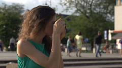 Girl doing photos on old camera in town, steadycam shot, slow motion shot Stock Footage