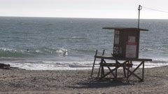 Surfers catching waves including getting a barrel by a life guard stand on a Stock Footage