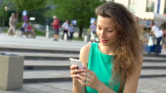 Happy girl texting messages on smartphone, steadycam shot, slow motion shot at 2 Stock Footage