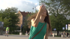 Happy girl recording herself on camera, steadycam shot, slow motion shot at 240f Stock Footage