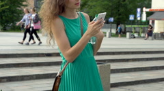 Happy girl texting on smartphone in the city, steadycam shot, slow motion shot Stock Footage