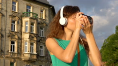 Concentrated girl listening music on headphones and doing photos on old camera Stock Footage