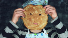 4k Colourful Shot of a Cook Child Posing Funny with a Pancake on Face Stock Footage