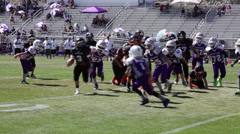 Ball carrier runs hard to right side for a few yards at youth football game,3608 Stock Footage