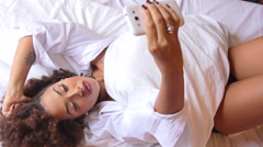 Beautiful Young Woman Lying in Bed Taking a Selfie Stock Footage