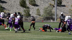 Good blocking opens hole for a run up the middle at youth football game,3609 Stock Footage