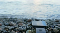 Blurred smart watches are near the pebble beach of the ocean. The clock reflects Stock Footage