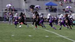 Ball carrier runs up the middle, hard tackle at youth football game,3614 Stock Footage