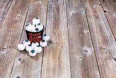 Bucket filled with eyeballs for Halloween season on rustic wood Stock Photos