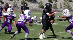 Defense hits ball carrier hard to bring him down at youth football game, 3615 Stock Footage