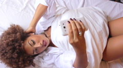 Sexy and Attractive Young Woman Lying in Bed Texting With a Mobile Stock Footage