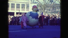 1948: clowns carry large yellow bird in cracked egg, marching band follows Stock Footage