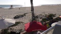 Pan up from party beach tents in front of oceanfront homes to palm trees bloc Stock Footage