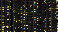 Time lapse of lights flickering windows in high density apartment block at night Stock Footage