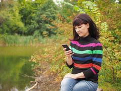 Beautiful young woman using smartphone at autumn park. Pretty young woman in  Kuvituskuvat