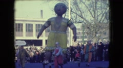 1948: parade displays turn a corner, santa, native american balloon, and a pink Stock Footage