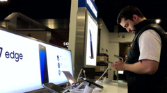 People playing Samsung Galaxy Note 7 cellphone at Best Buy store Stock Footage