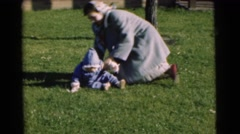 1951: a mother wrestling with her baby in the front yard on the lawn CHATHAM, Stock Footage