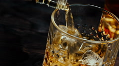 Barman pouring whiskey in the glass with ice cubes on wood table Stock Footage