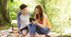 4k, Young couple using a digital tablet together while out on a romantic picnic Stock Footage