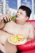 Fat man enjoy junk food in winter season Stock Photos