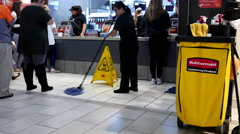 People ordering food and worker cleaning floor at mcdonalds check out counter Stock Footage