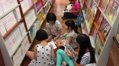 Children choose and read books at the bookstore Stock Footage