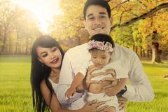 Parents and their child at autumn park Stock Photos