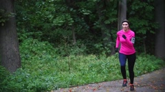 Runner young woman running in autumn park exercising outdoors at gloomy weather Stock Footage