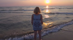 MED Young woman standing in water and watching the sunset over the sea. 4K UHD Stock Footage
