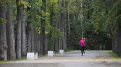 Runner young woman running in autumn park exercising outdoors at rain, pink Stock Footage