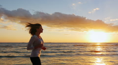 Young attractive woman jogging on the beach at sunset. Beautiful clouds and Stock Footage
