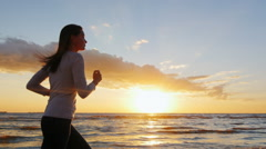 Young woman with a beautiful figure running on the beach at sunset. Long hair is Stock Footage