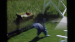 1951: two toddlers, one in blue and the other in yellow, happily playing outside Stock Footage