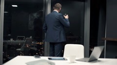 Young businessman drinking whiskey and admire view form window in office at nigh Stock Footage
