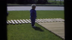 1951: two toddlers playing on a grass courtyard with wooden walkways CHATHAM, Stock Footage