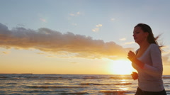 Attractive young woman is running along the seashore at sunset. Engage in sports Stock Footage