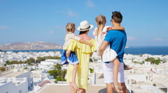 Family in Europe. Parents and kids background the old town in Mykonos island Stock Footage