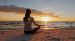 No stress. Calm young woman sitting in a lotus position on the beach at sunset Stock Footage