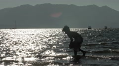Silhouette Boy Catching A Ball On The Shore  Stock Footage